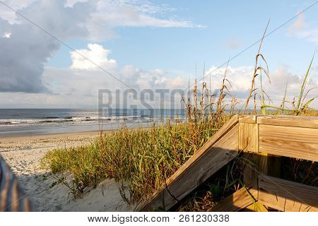 At The End Of A Wooden Boardwalk Path Through The Sand Dunes To The Atlantic Ocean Beach, Sunset Bea