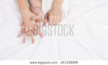 Sensual beautiful young couple is having sex on bed. Female hand pulling white sheets in ecstasy, orgasm. Love concept. Wellness. Couple in love. Orgasm concept. poster