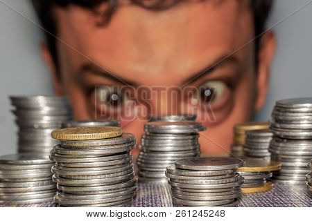 Focus On Coin. A Rich Greedy Elderly Man Looks At Coins. The Collector Looks At His Wealth. An Elder