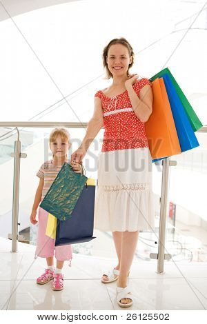young mother with little daughter in mall with baf