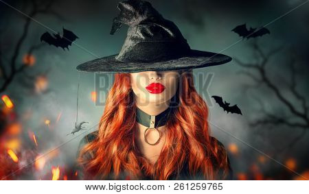 Halloween Sexy Witch girl portrait. Beautiful young woman in witches hat with long curly red hair and bright lips makeup. Over spooky dark magic forest background. Wide Halloween party art design