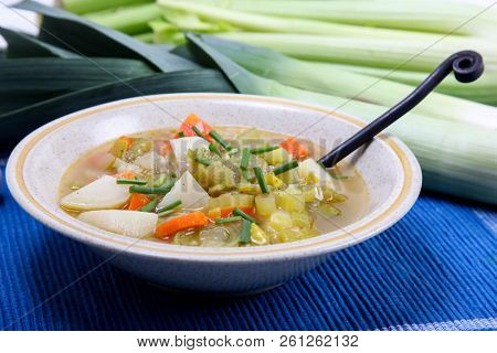 Leek soup with potato on blue background with leek