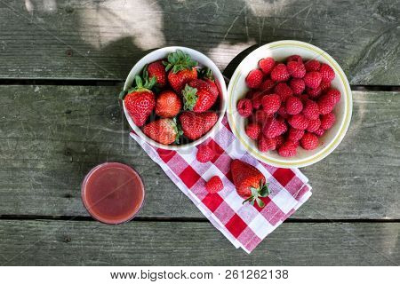 Raspberries   strawberries inside bowls on wooden table with vitamin drik