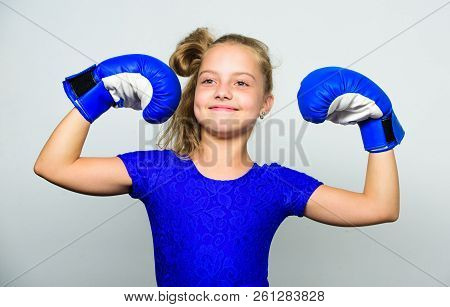 Girl Child Happy Winner With Boxing Gloves Posing On Grey Background. She Feels As Winner. Upbringin