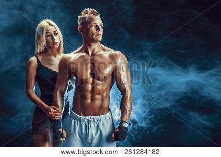 Attractive Couple, A Slim Blonde Female And Handsome Shirtless Guy Posing In Studio On A Dark Textur