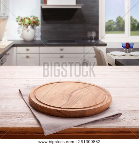 Empty Wooden Table With Pizza Board And Tablecloth Near The Window In Kitchen. White Napkin Close Up