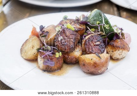 Blackened Scallops Served With Cooked Potatoes, Zucchini And Garnished With Arugula Sprouts