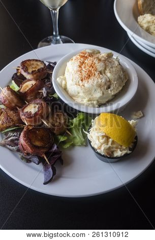 Grilled Bacon Wrapped Scallops Served With Coleslaw And Creamy Potato Salad