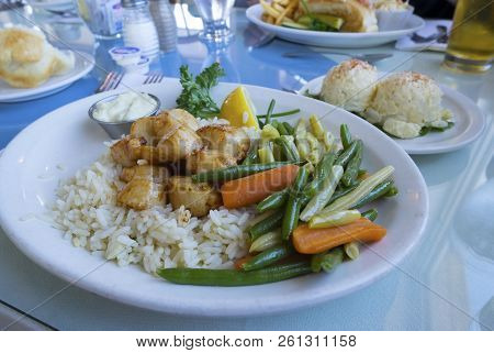 Cooked Scallops Served With Beans And Baby Carrots On A Bed Of Rice, With Side Of Creamy Potato Sala