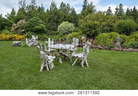 Sculptures Of Chairs And Tables In A Formal Garden