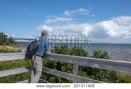 Man Looking At The Confederation Bridge From Cape Jourimain, New Brunswick, Canada