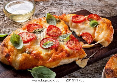 A Delicious Rustic Homemade Pizza Margherita With Fresh Mozzarella Cheese, Roma Tomatoes And Basil.