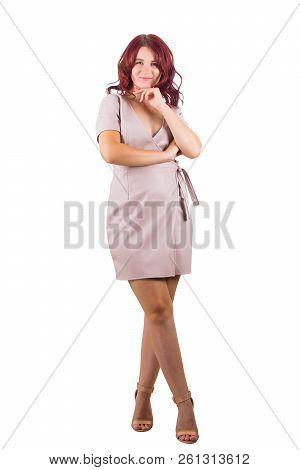Full Length Portrait Of Beautiful Young Redhead Woman Holding Hand Under Chin And Crossed Legs Looki