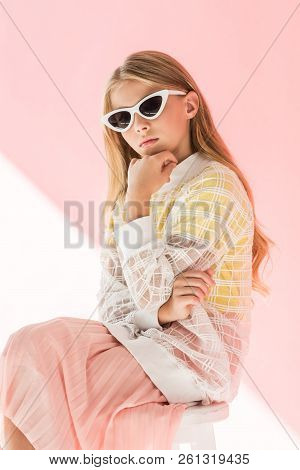 adorable fashionable youngster in trendy sunglasses posing on pink poster