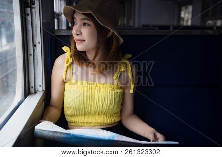 Young Asian Woman Sitting On Train Holding Map At Train Station. Lady Passenger Traveling By Train L