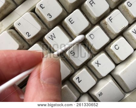 Person Cleaning Dirty Keyboard Keys With A Cotton Bud