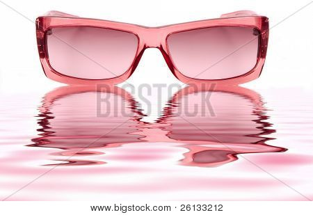 A pair of pink ladies sunglasses isolated on a white background and reflecting in water ripples