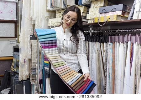 Adult Woman The Owner Of The Interior Fabrics Store, With Fabrics Samples.