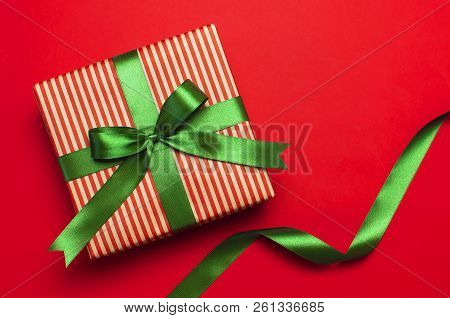 Gift Box With Green Ribbon On Red Background Top View Flat Lay. Holiday Concept, Birthday Gift, New
