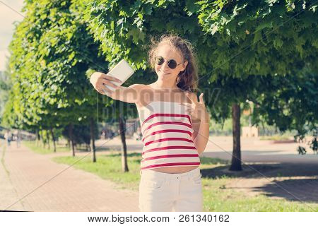 Young Teen Girl Having Fun With The Phone, Takes A Video, Takes A Selfie.
