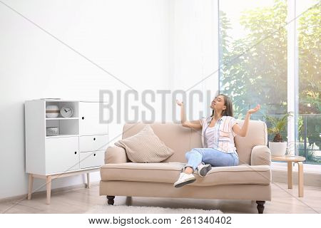 Young Woman Relaxing Under Air Conditioner At Home