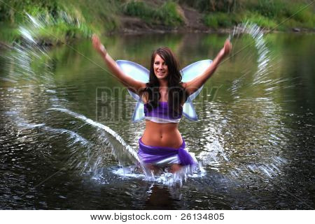 Beautiful brunette fairy playing in a river