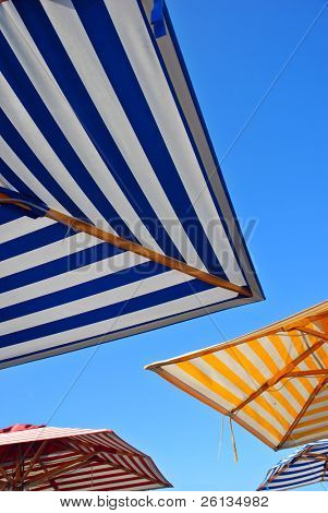 Three picnic table umbrellas in different colors outdoors set against a clear blue sky