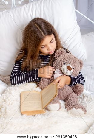 Little girl lying on the bed with her favorite teddy bear and reading a book before bedtime poster