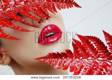 A Woman With Sensual Red Lips And A Fern