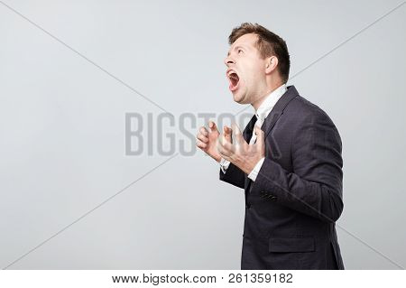 Side View Of Young Caucasian Man Screaming Loudly While Standing Isolated On Gray Background With Co