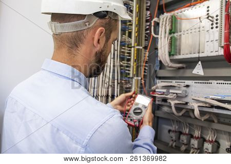 Young Adult Electrician Builder Engineer Inspecting Electric Equipment In Distribution Fuse Box. Ele
