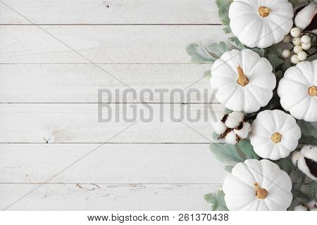 Autumn Side Border Of White Pumpkins And Silver Leaves Over A Rustic White Wood Background