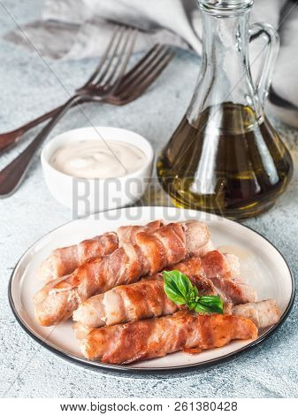 Ready-to-eat Pigs Sausages Wrapped In Bacon On Plate. Fried Savory Sausages Wrapped In Bacon Served