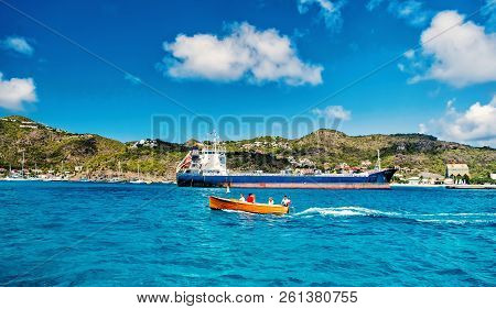 St. Barts - January 01, 2016: People Sailing In Small Boat Against Big Cargo Ship Or Barge In French