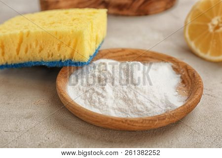 Bowl With Baking Soda And Sponge On Gray Table