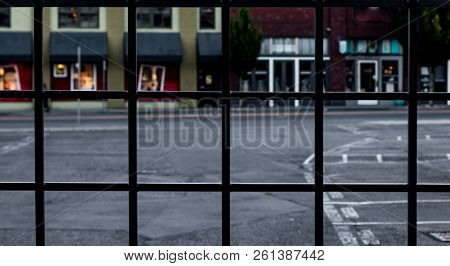 Wrought Iron Fence Abstract With Retail Buildings Blurred In The Background