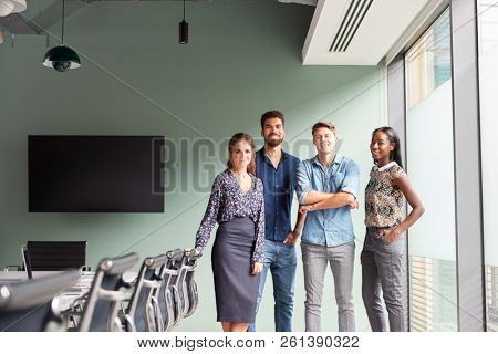 Portrait Of Casually Dressed Businessmen And Businesswomen Having Informal Meeting In Modern Boardroom