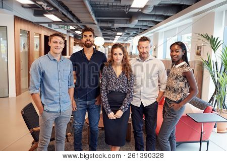 Portrait Of Casually Dressed Businessmen And Businesswomen In Modern Office Space
