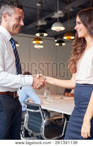 Businessman And Businesswoman Shaking Hands In Modern Boardroom With Colleagues Meeting Around Table In Background