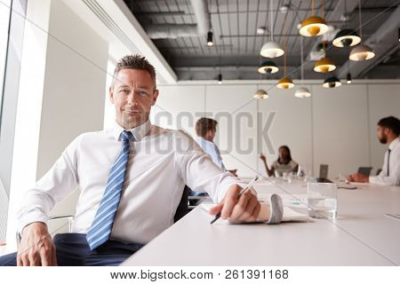 Portrait Of Mature Businessman Sitting In Modern Boardroom With Colleagues Meeting Around Table In Background