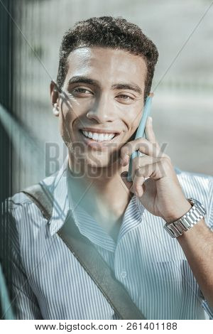 Jovial Gay Guy Discussing Plans On Smartphone