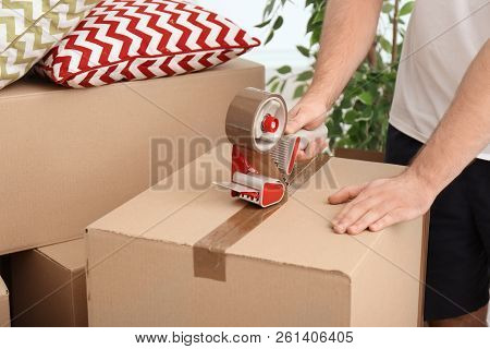 Man Packing Carton Box Indoors, Closeup. Moving Day