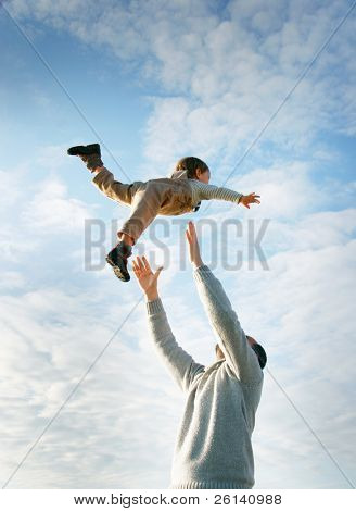 happy father and son playing on sky background poster