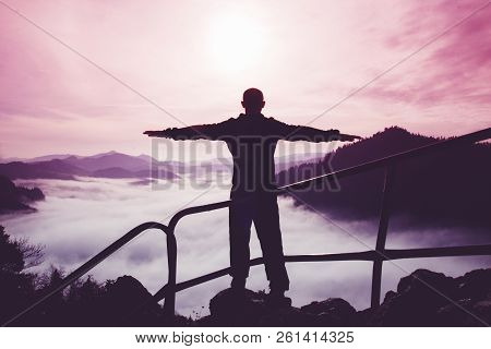 The Silhouette Of A Single Man With Arms Apart Standing On Top Of A Mountain Against A Surreal Purpl