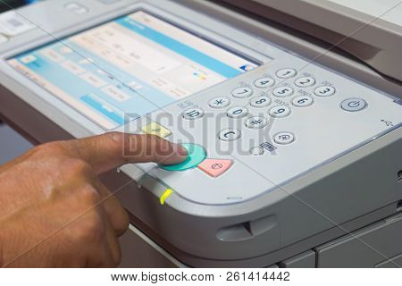 man finger pressing the start button on a multifunction couler printer or copier. poster