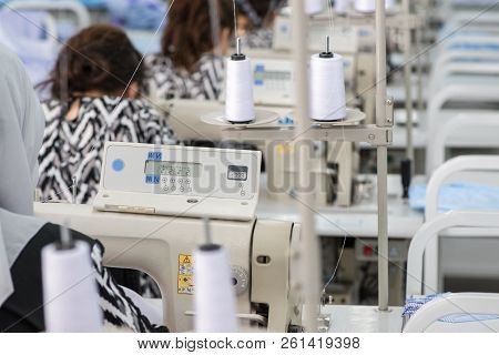 Women In The Textile Factory. Workers In The Sewing Workshop Working On A Sewing Machine