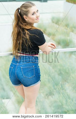 Back View Of Young Teenage Woman Wearing Short Blue Jeans Denim Shorts Enjoying Summer Weather