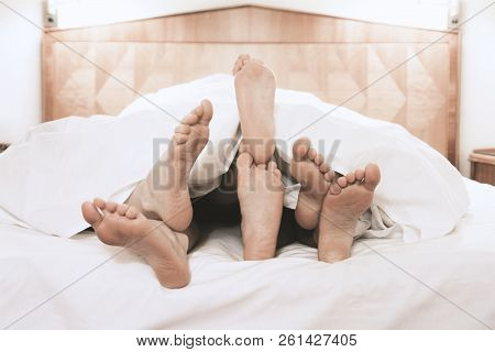 Three Pairs Of Feet Lying Together Under Bed Cover In Bedroom, Threesome Group Sex Concept, Filtered