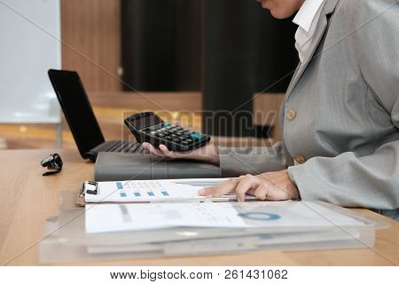 financial adviser working with calculator, business document at office. accountant doing accounting & calculating revenue & budget. bookkeeper making calculation. finance & economy concept poster
