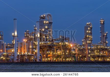 A petrochemical plant, with it's stainless steel cylinders, it's valves, chimneys, pipes, tubes and construction artificially lit just before the break of dawn